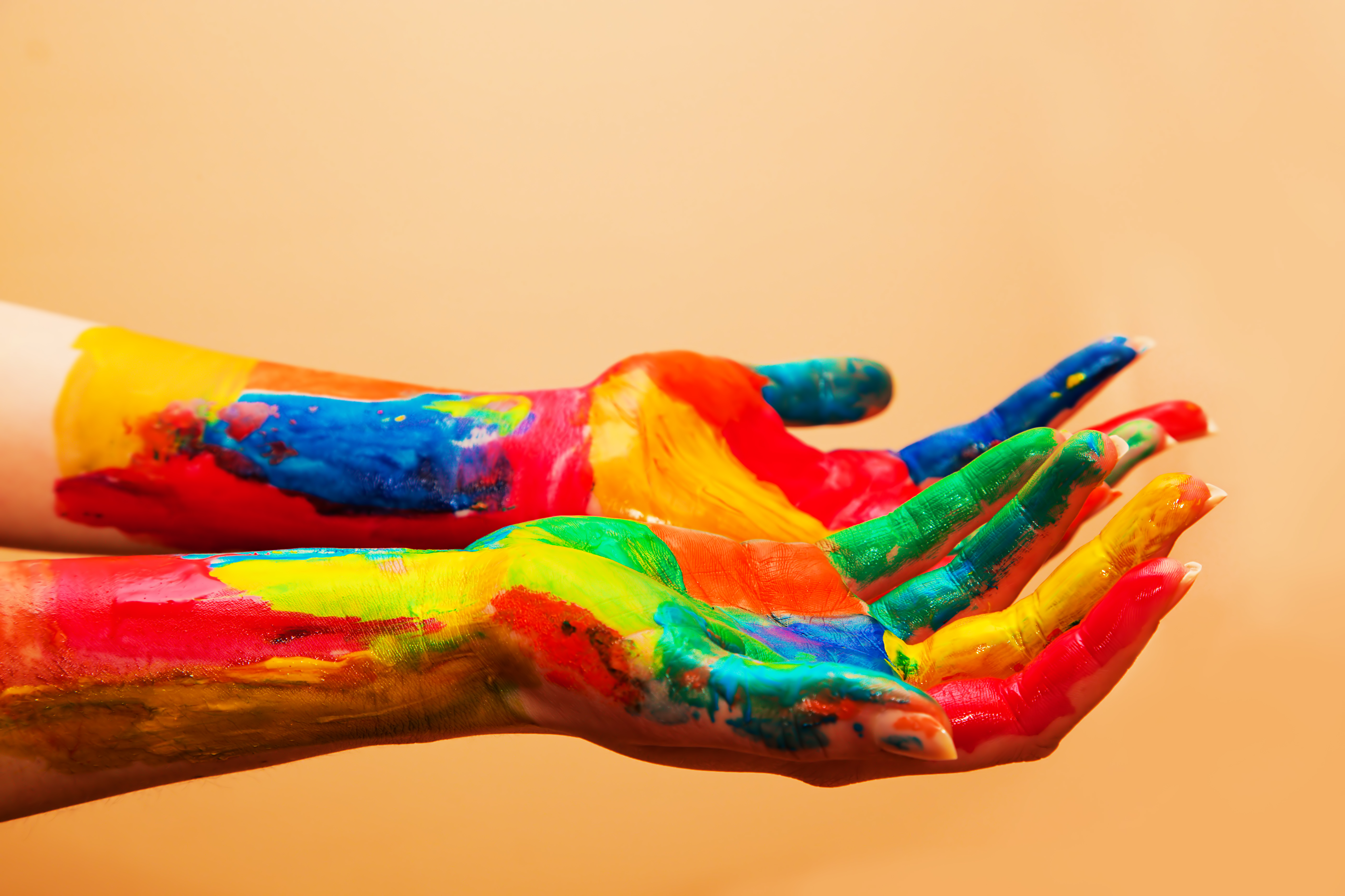 Painted hands, colorful fun. Creative, funny and artistic means happy! Orange background wall