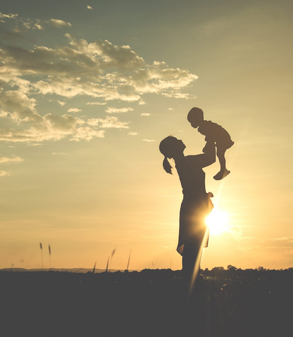 A silhouette of a happy young mother harmonious family outdoors. laughing and playing in the summer on the sunset background